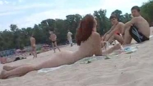 Naked girls are playing with each other in the sand and sitting on each other's wide seat